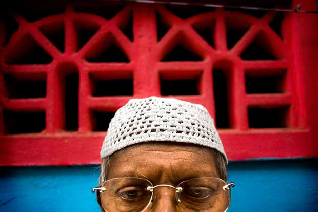 Portrait of a man wearing glasses in front of a house painted in blue and red taken by photographer Biel Caldrón Rincón