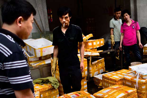 A group of Asian men smoking cigarettes on a market photographed by documentary photographer Biel Calderón Rincón