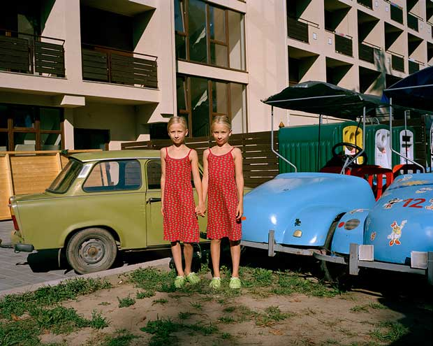 Picture of a young twin couple in front of some old colorful cars photographed by Michal Solarski