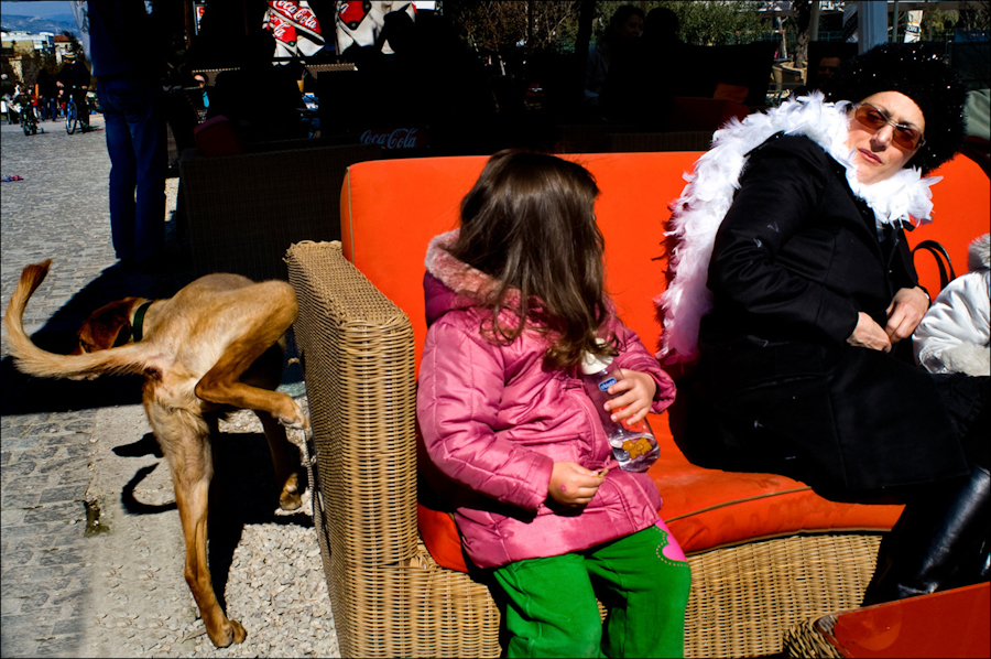 Image taken by street photographer Alexis Vasilikos of a girl and a woman sitting on a bench while dog is peeing on the side