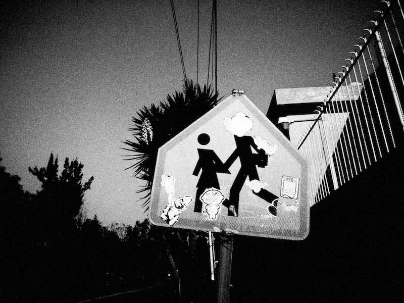 Black and white street sign covered with stickers photographed by Alex Coghe