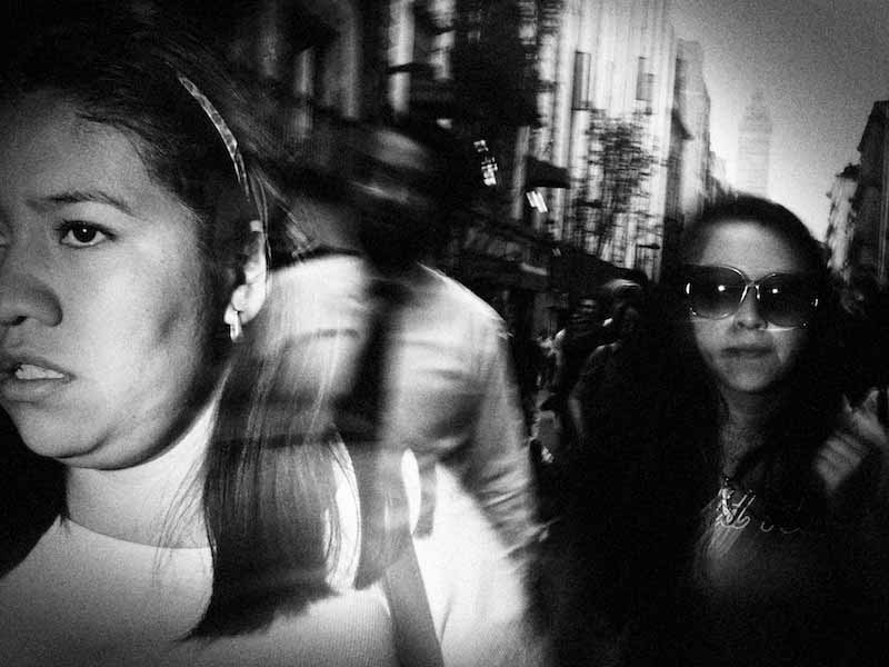 Blurry black and white image of people walking on the street captured by Alex Coghe