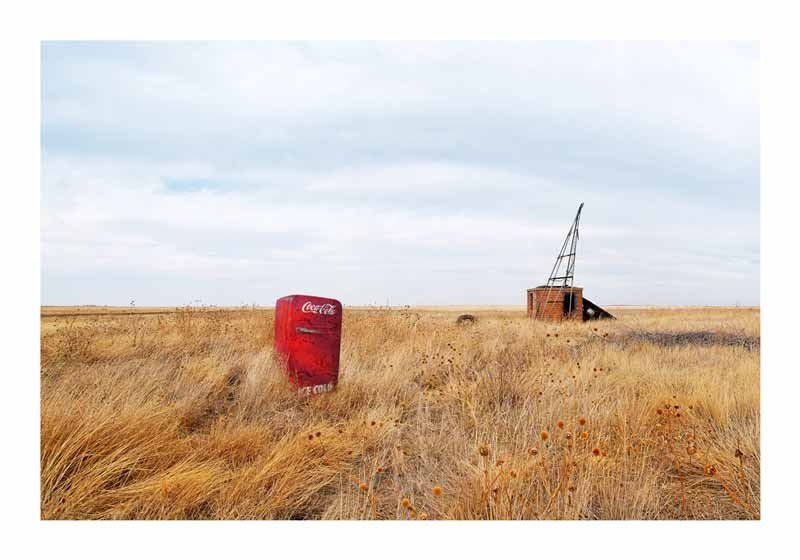 On this image from Serio Fasola one can see a red freezer with coca cola written on it placed in midst of a field