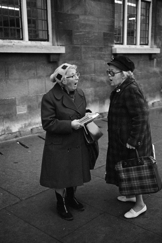Street photographer Chris Porsz photographed two women talking to each other on the street