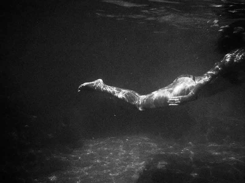 A young girl swimmimg in the water under the surface captured by Emilio Barillaro