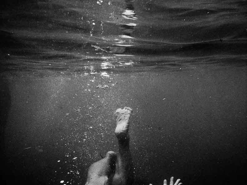 A foot of a girl sticking up under water as she sinks down