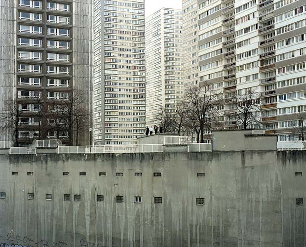 The front side of a huge grey colored apartment building captured by Antoine Séguin