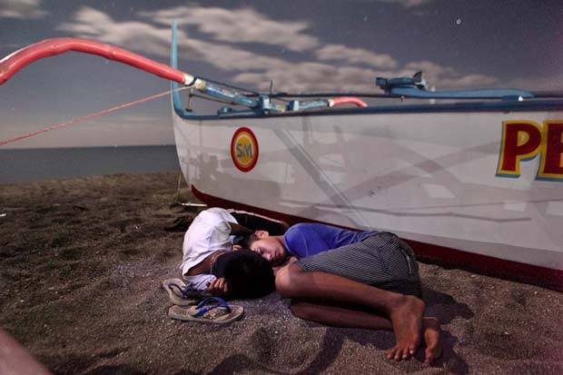 Geric Cruz and his image of two young boys sleeping next two a fisher boat