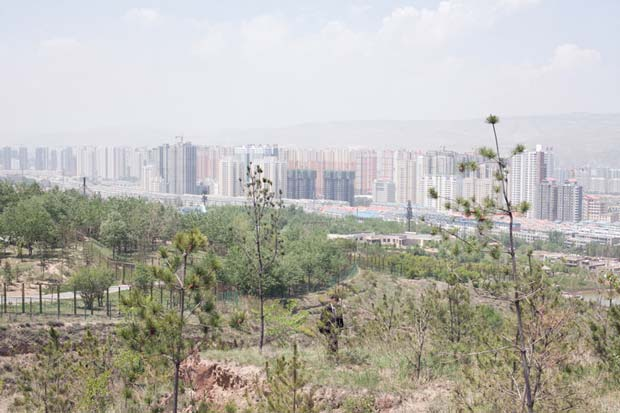 A grey skyline of high apartment buildings in China photographed by John Francis Peters for his series Western China