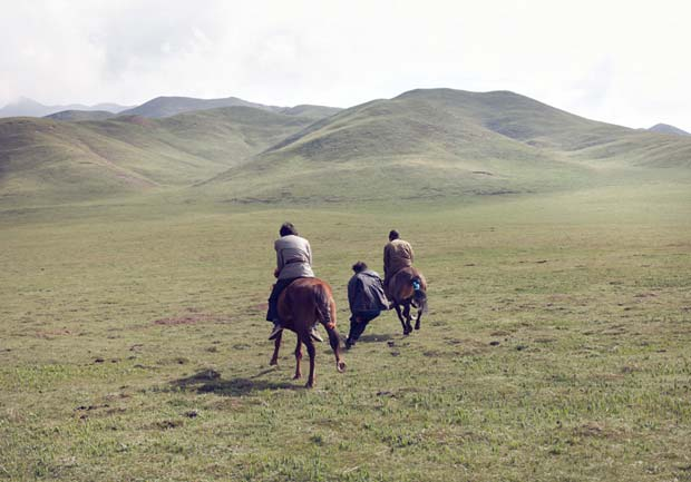 A group of men riding through the great plains in China on their horses