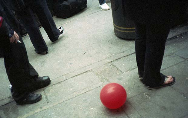 A red ball on the floor surrounded by black feet captured by Marc Fairhurst