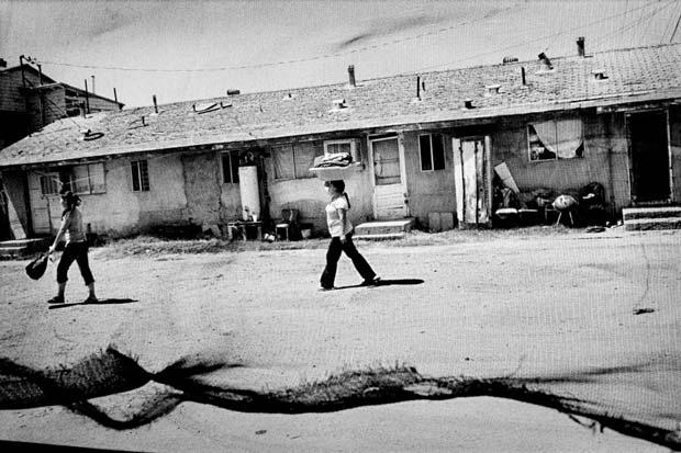Photograph from Matt Black showing a woman crossing a street