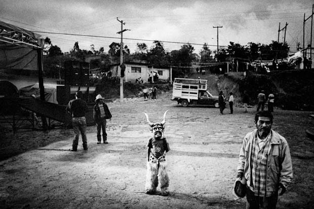 A boy with a mask standing in the middle of dusty road photographed by documentary photographer Matt Black