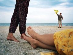 Two pairs of feet and a young boy playing in the background on a beach captured by street photographer Maxim Chichinskiy