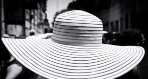 A woman wearing a giant white hat photographed by street photographer Manuel Chavez from Argentina