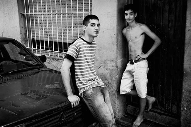 Street photography from Argentina showing two young guys hanging out outside of their house on this image from Manuel Chavez