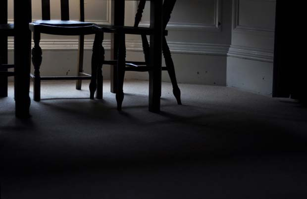 A table and some chairs standing in an empty low lit room photographed by Alison Gibson for her series called The Castle