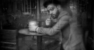 Image of a man sitting in a cafe taken by Darran Roper street photographer