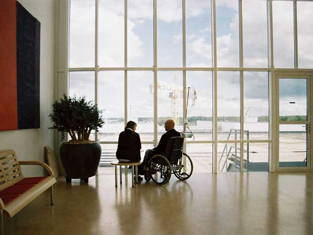 Image of man in a wheelchair next to window taken by Maarten van Riel