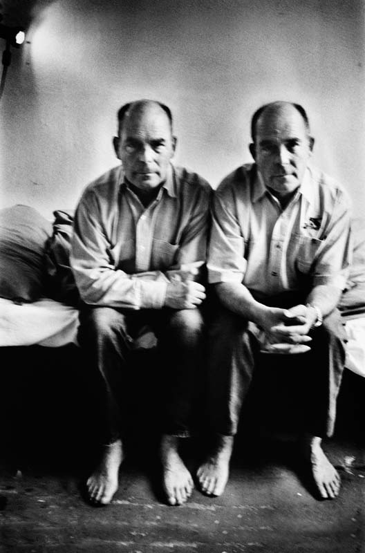 "Two man sitting on a bed on this image taken by Margaret M. de Lange for her book ""Surrounded By No One"""