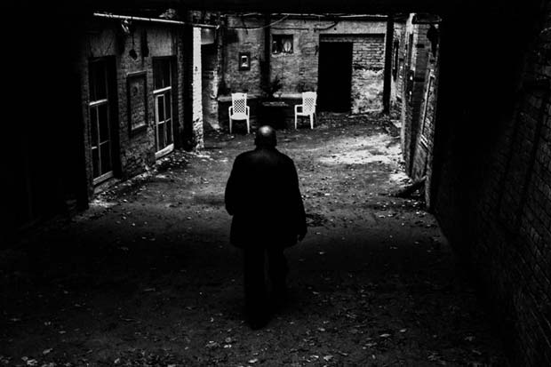A lonely man walking through a hallway into a yard on an image taken by Matjaz Rust photography