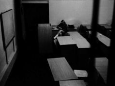 A student sitting in an empty lecture room captured by Matjaz Rust photography
