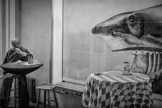 Picture of a shark and a man eating in a fast-food place photographed by Enrico Markus Essl street photography