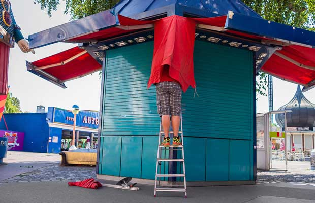 Funny image of a man under a red cloth taken by Enrico Markus Essl street photography