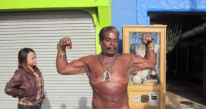 A muscled man in a bathing suite in the colors of the US flag showing off his muscles photographed by Julie Grace Immink
