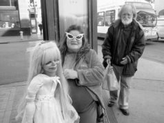Woman at a bus stop next to a doll wearing funny looking extravagant glasses photographed by Julie Grace Immink photography
