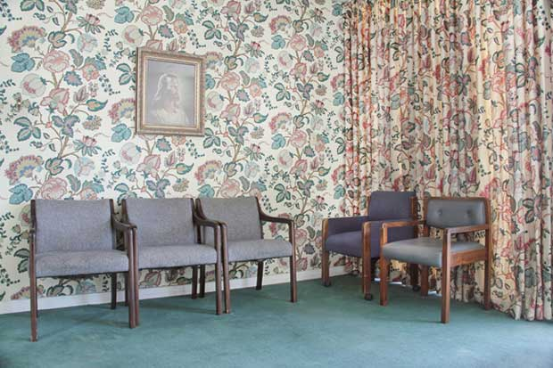 Picture of an empty waiting room with flower wall-paper and empty chairs taken by Julie Grace Immink photography
