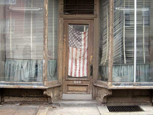 An old American flag hanging in a shut-down shop window in Brooklyn New York captured by Julie Grace Immink photography