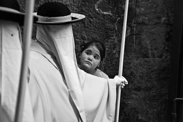 A girl looking with surprise at a man covered in a white robe photographed by Luca Napoli street photography