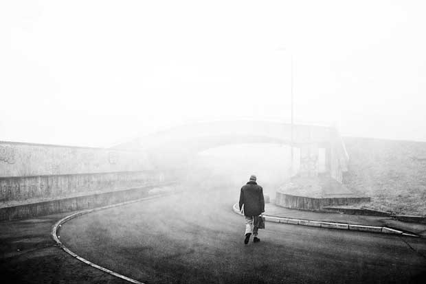 A lonely man walking off into the fog captured by street photographer Luca Napoli