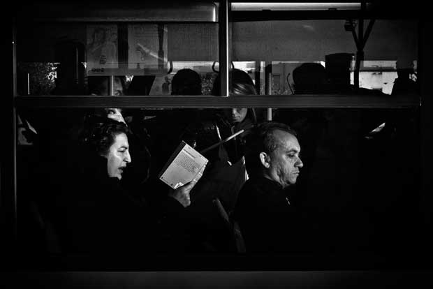 A woman reading a book on a crowded bus photographed by Luca Napoli street photography