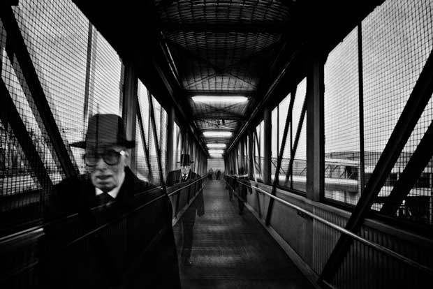 Double exposure of a man crossing a bridge taken by street photographer Luca Napoli