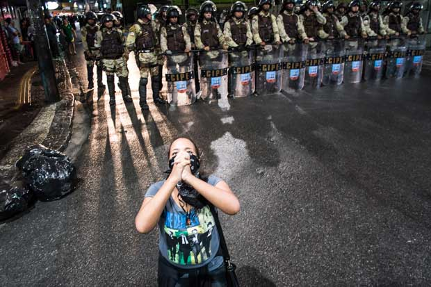 A young girl at a demonstration against the FIFA World Cup in Salvador da Bahia backed by a group of military police officers.