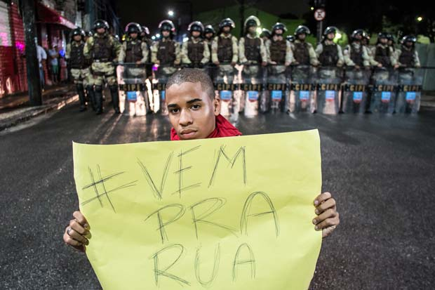 """Vem pra rua"" - ""Come to the streets"": A young boy at a demonstration against the FIFA World Cup in Salvador da Bahia backed by a group of military police officers."