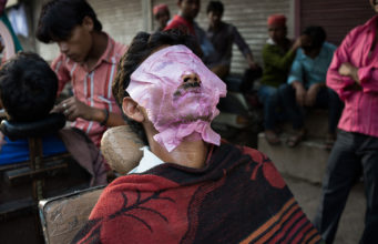 Street Photography in India by Pushkar Raj Sharma: A man with a pink mask sitting on the streets