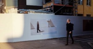 A blond man in a black outfit is walking by a big advertisement showing a fashion model. Image from street photographer Siddhartha Mukherjee.