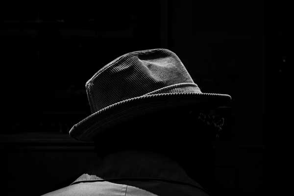 Image of a man with a hat taken by L.A. based street photographer Rinzi Ruiz who is known for his street zen approach to taking pictures in urban surroundings